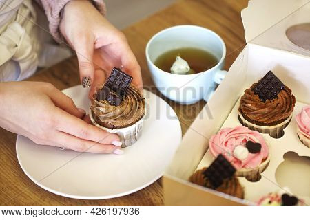 High Angle Of Blurred Unrecognizable Female Sitting At Table With Sweet Delicious Cupcake And Cup Of