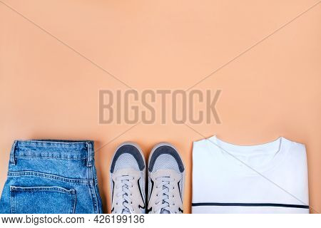 Sport Inspired Flatlay With White Striped T-shirt, Blue Sneakers And Denim Shorts Isolated On Beige