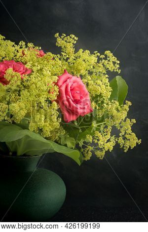 A Flower Arrangement With Pink Roses In A Round Vase Against A Moody Dark Background