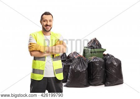 Waste collector in a uniform and gloves posing in front of a bin and pile of bags isolated on white background