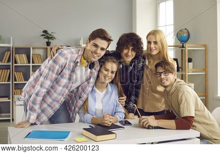 Smart And Modern High School Or College Students Sitting And Standing At A Desk In The Classroom.