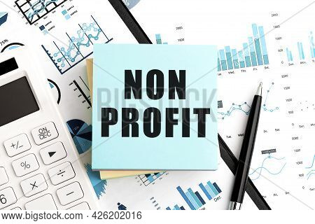 Text Non Profit On Stickers. Pen And Calculator On Clipboard With Charts, Documents And Graphs. Busi