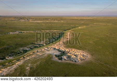 sunset light over arroyo and badlands in Pawnee National Grassland in northern Colorado, early summer scenery aerial view