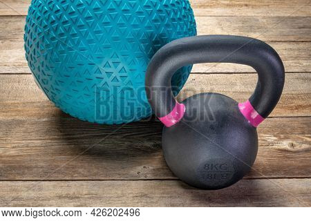 heavy rubber slam ball filled with sand and  small iron kettlebell on a rustic wood background,  training, exercise and fitness concept