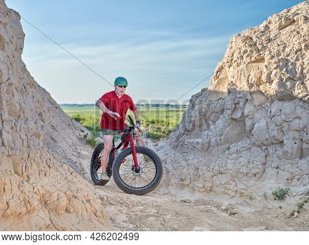 Senior man is riding a fat mountain bike in badlands of Pawnee National Grassland in northern Colorado