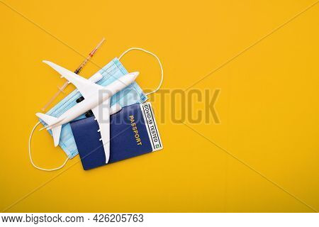 Syringe, Toy Plane, Medical Mask And Passport With Covid-19 Test  With Text 'covid-19 Tested' Inside