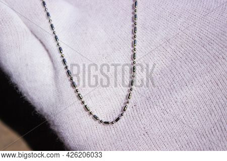 Woman As Salesperson Behind Counter In Jewelry Store. Holds Set Of Chains