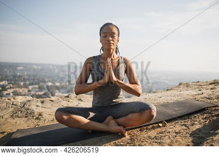 Smiling American Woman Sitting In Lotus Position, Eyes Closed And With Namaste Gesture With Cityscap