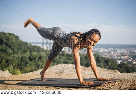 Positive African Woman In Sport Clothes Doing Morning Exercise On Yoga Mat Outdoors, Legs Lifting. H