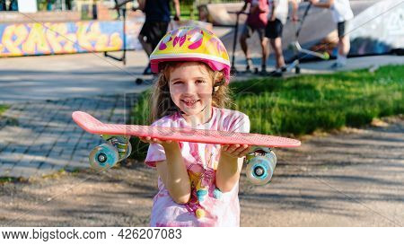 Sportive Girl Holding A Pennyboard In Her Hands And Smiling. Schoolgirl Girl Spends Summer Holidays