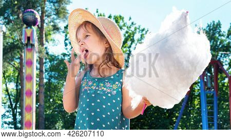 Cute Little Girl Eating A Huge Piece Of Cotton Candy In An Amusement Park On A Summer Day. Happy Chi