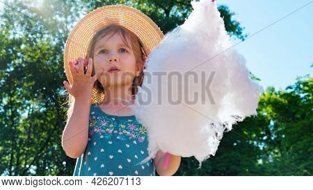 The Girl Looks In Amazement And Surprise At The Amusement Park. A Child Eats Cotton Candy On A Sunny