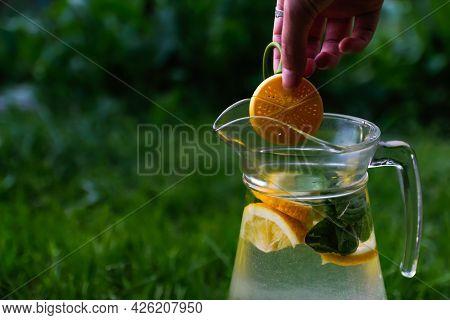 Defocus Hand Holding Dummy Lemon Hanging Over Glass Jug Of Lemonade With Slice Lemon And Leaves Of M