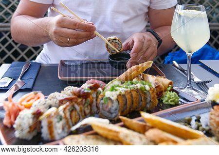 Eating Sushi With Chopsticks At Sushi Restaurant
