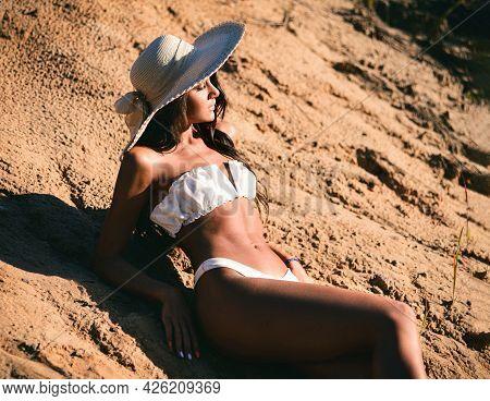 Slim Sexy Woman In White Bikini And A Hat On The Beach. Pretty Sensual Summer Brunette Model With Ta
