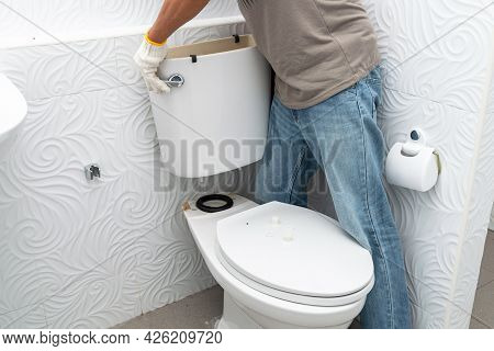 Man Worker Repairing With Toilet Tank In Bathroom, Close-up,  Photography Grain, Noise.