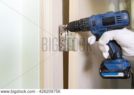 A Man With A Tool Repairs Castle Doors,  Repair The Bathroom Door With A Drill