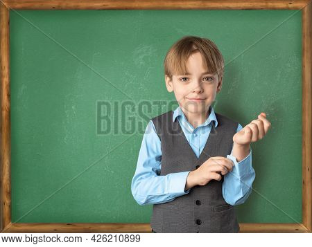 Concept Back To School. A Caucasian Boy Pupil In Front Of The Classroom Board In A School Uniform Pr