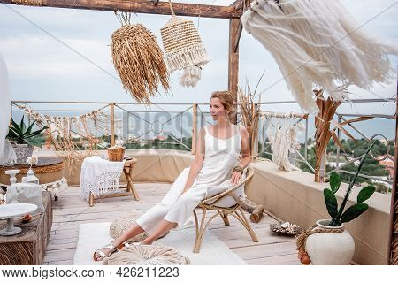 A Young Woman In A Fashion White Jumpsuit Sits On A Vintage Vine Chair On An Outdoor Rooftop Terrace