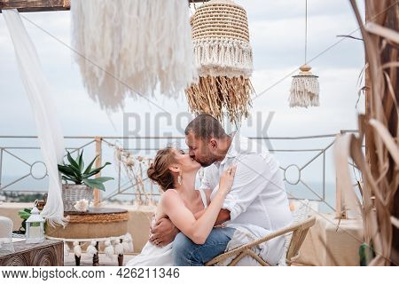 Close Up Portrait Of The Happy Middle-aged Couple In White Kissing On The Floor On The Open Terrace