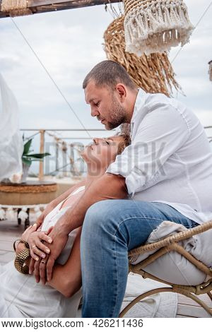 Close Up Portrait Of The Happy Middle-aged Couple In White Hugs On The Floor On Open Terrace Of The