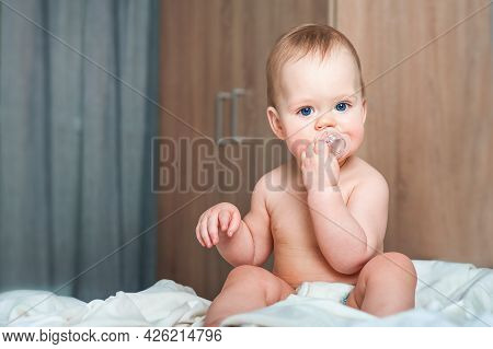 Lovely Baby With A Pacifier On The Bed In The Bedroom. Children's Sleep, Malocclusion, Teething