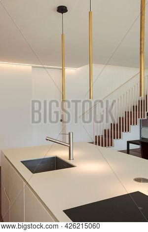 Detail of modern design kitchen with black induction cooking, sink in stainless steel, and design lamp. In background there are a close door and cantilever staircase. White wall. Nobody inside