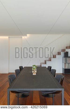 Frontal view of modern dark table with chair. in background there are cantilever staircase and library. Luxury wooden floor. Interior of design apartment. Above there is space for text.