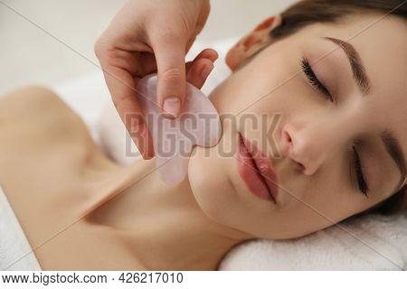 Young Woman Receiving Facial Massage With Gua Sha Tool In Beauty Salon, Closeup