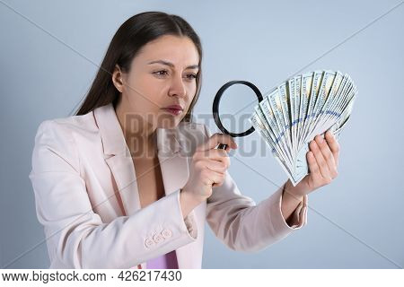 Expert Authenticating 100 Dollar Banknotes With Magnifying Glass On Light Grey Background. Fake Mone