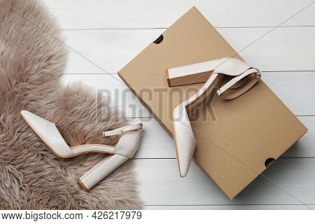 Pair Of Stylish Shoes, Cardboard Box And Faux Fur On White Wooden Background, Flat Lay