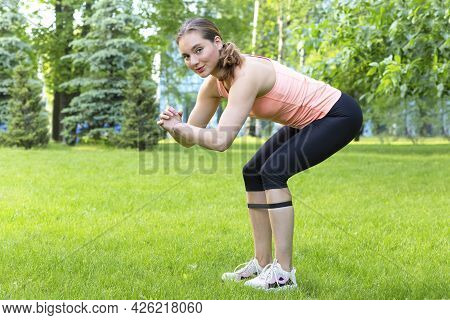 Fitness Trainer Woman With Resistance Rubber Band Doing Squats, Stretching In Park Outdoors. Athleti