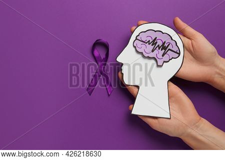 Top View Of Woman Holding Paper Human Head Cutout With Brain Near Purple Ribbon On Color Background,