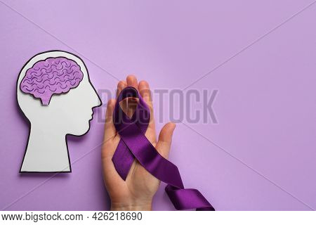 Woman Holding Purple Ribbon Near Paper Human Head Cutout Over Violet Background, Top View. Epilepsy