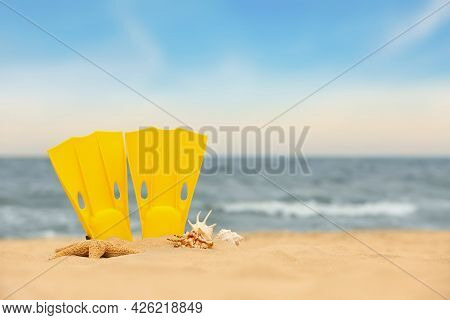 Yellow Flippers And Seashells On Sand Outdoors, Space For Text. Beach Objects