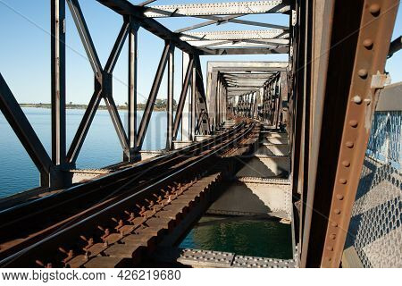 Rail Lines Lead And Curve Through The Structure Of Steel Truss Bridge, Tauranga New Zealand.