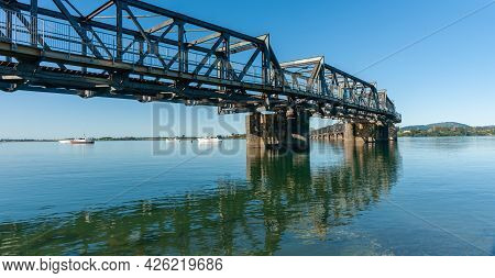 Curving Lines Of Historic Steel Truss Railway Bridge Leading Across Tauranga Harbour From City To Ma