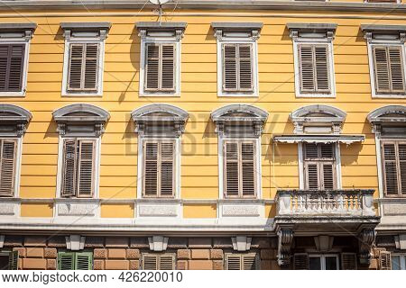 Typical Italian Mediterranean Facade Of A Residential Building, Yellow, With Traditional European Wo