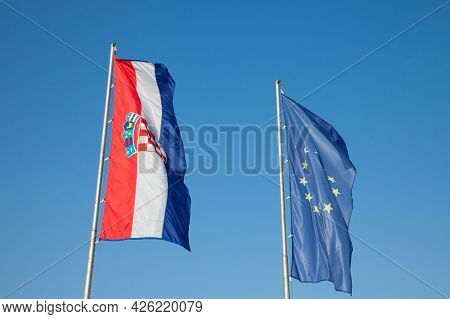 Croatian And European Flags Waiving In The Air With A Blue Sky Background. Croatia Is The Youngest C