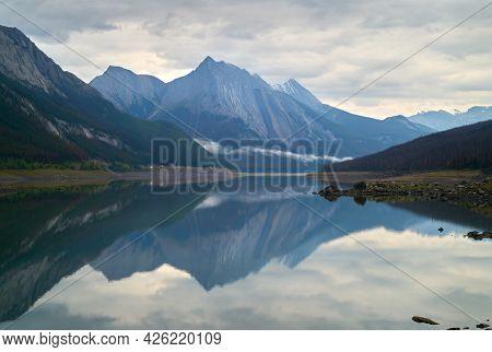 Medicine Lake Reflection Alberta. Medicine Lake Reflection Of Fresh Snow On The Surrounding Peaks. A