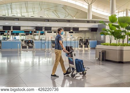 Man In Mask At Empty Airport At Check In In Coronavirus Quarantine Isolation, Returning Home, Flight