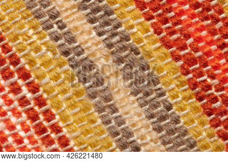 a small handmade rug or mat, woven from red and yellow wool threads, one object close-up