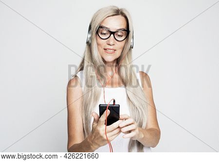 lifestyle, emotion and old people concept: Elderly woman with long white hair wearing white tshirt listening to music with headphones over grey background