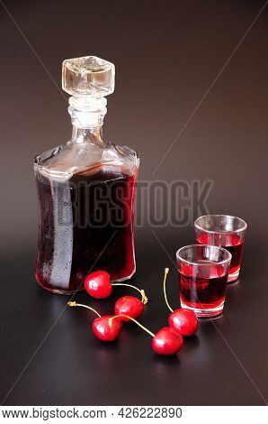 Cherry Liqueur With Ripe Berries In A Bottle And Glasses On A Black Background.