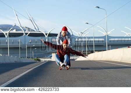 Happy Carefree Woman Sit On Longboard While Man Pushing Her Back Riding On Empty City Street. Young