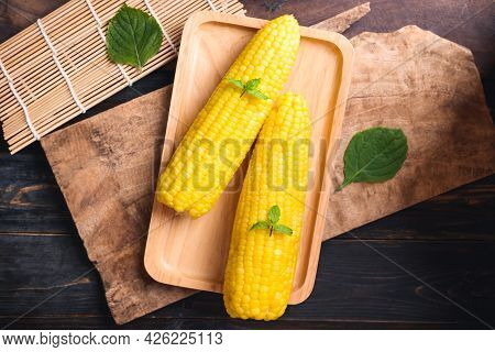 Sweetcorn Cob On Wooden Plate And Wooden Background, Top View
