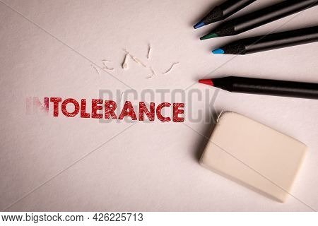 Tolerance. Colored Pencils And Eraser On A White Sheet Of Paper