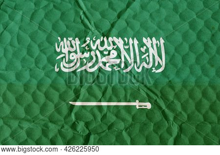 Green Flag Of Saudi Arabia On An Uneven Textured Surface. National Flag Of The State Located On The