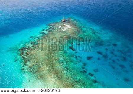 Shallow Waters Of Persian Gulf, Saudi Arabia. Red Warning Beacon With Triangle Top Mark Stands On A
