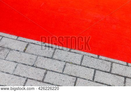 Red Carpet Lays Over Gray Cobbled Road, Background Photo Texture